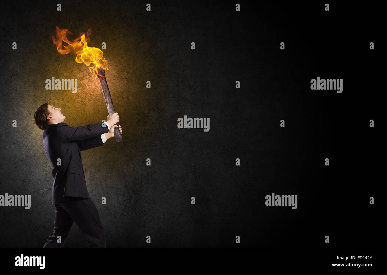 young businessman holding burning torch in hand stock photo stock photo young businessman holding burning torch in hand