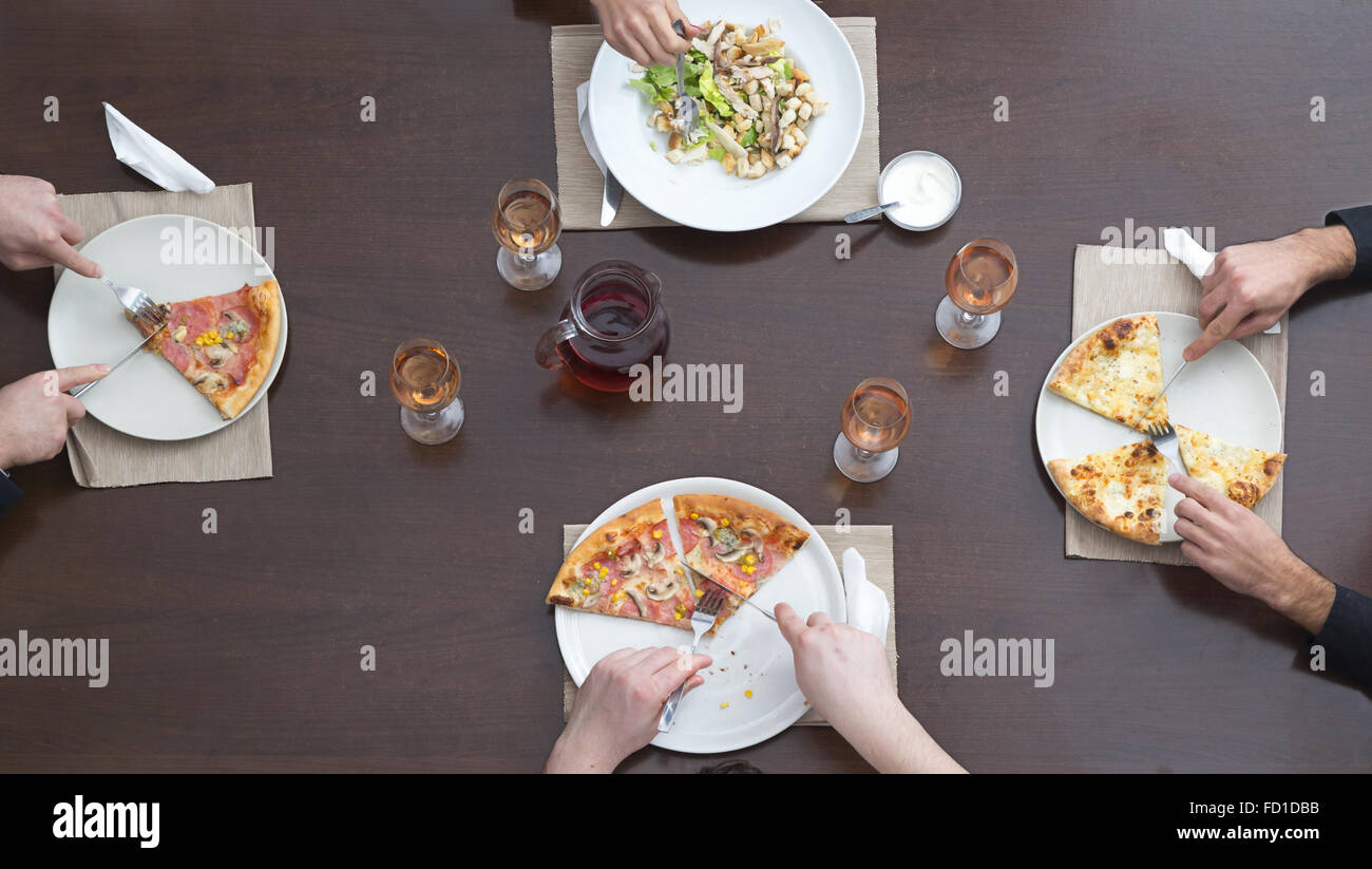 Dinner table top view - Top View Of Friends Eating Pizza And Salad On A Wooden Table In A Restaurant