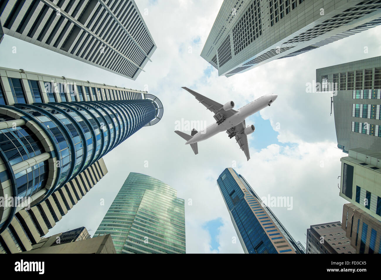 Tall city buildings and a plane flying overhead in morning Stock