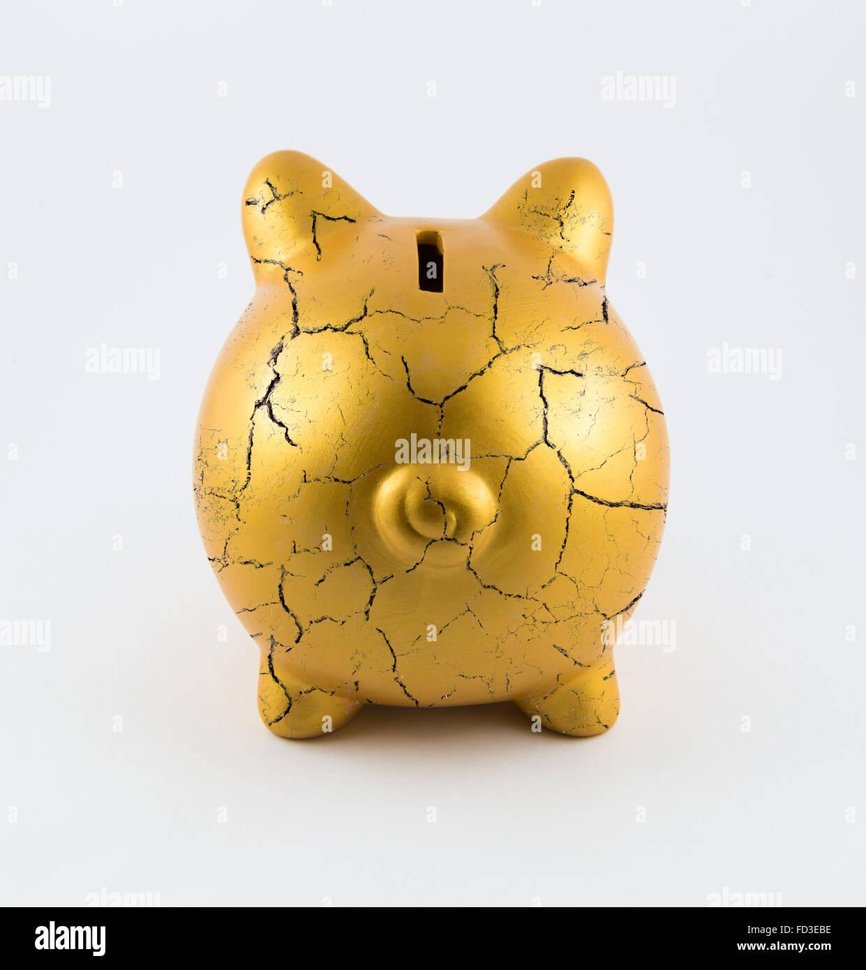 back side of gold piggy bank cracked on isolated white background  - back side of gold piggy bank cracked on isolated white background