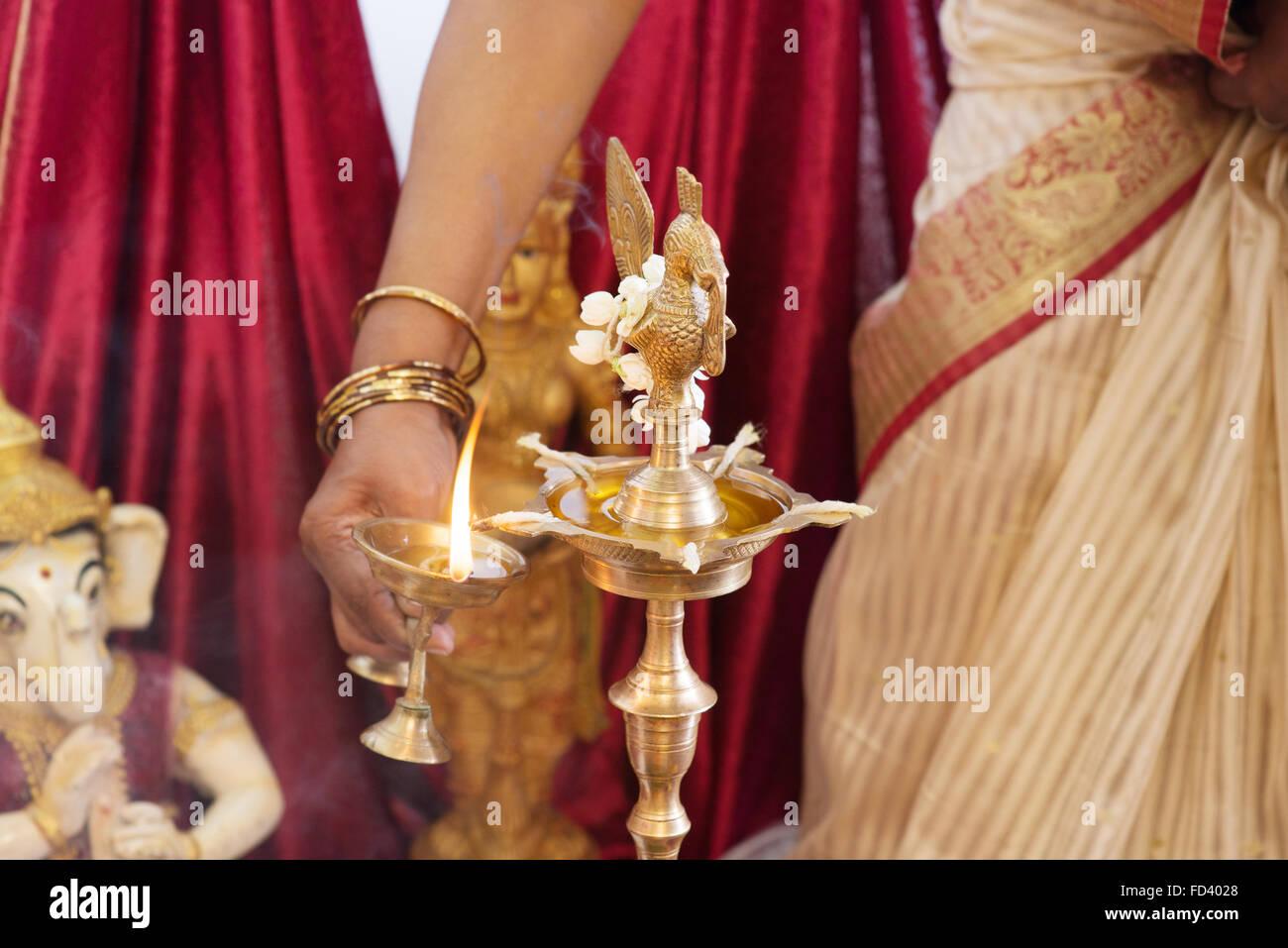 Woman lighting up the metal diya. Traditional Indian Hindus ... for Lamp Lighting Ceremony  303mzq