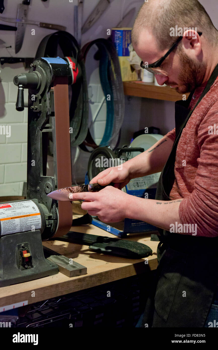 man sharpening kitchen knife on belt sander usa stock photo