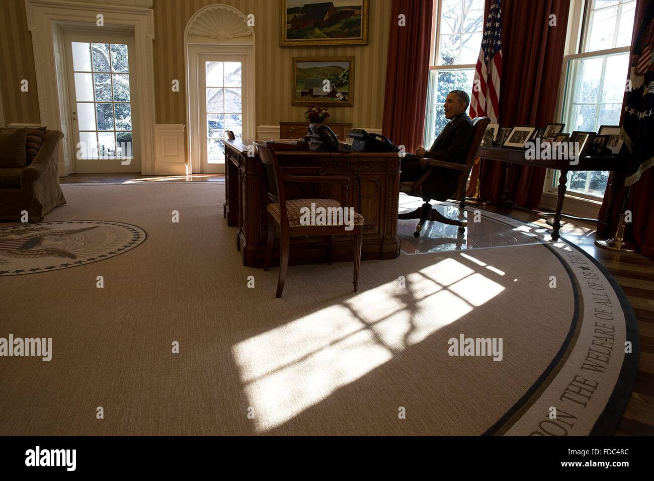 US President Barack Obama sits at the Resolute Desk as sun