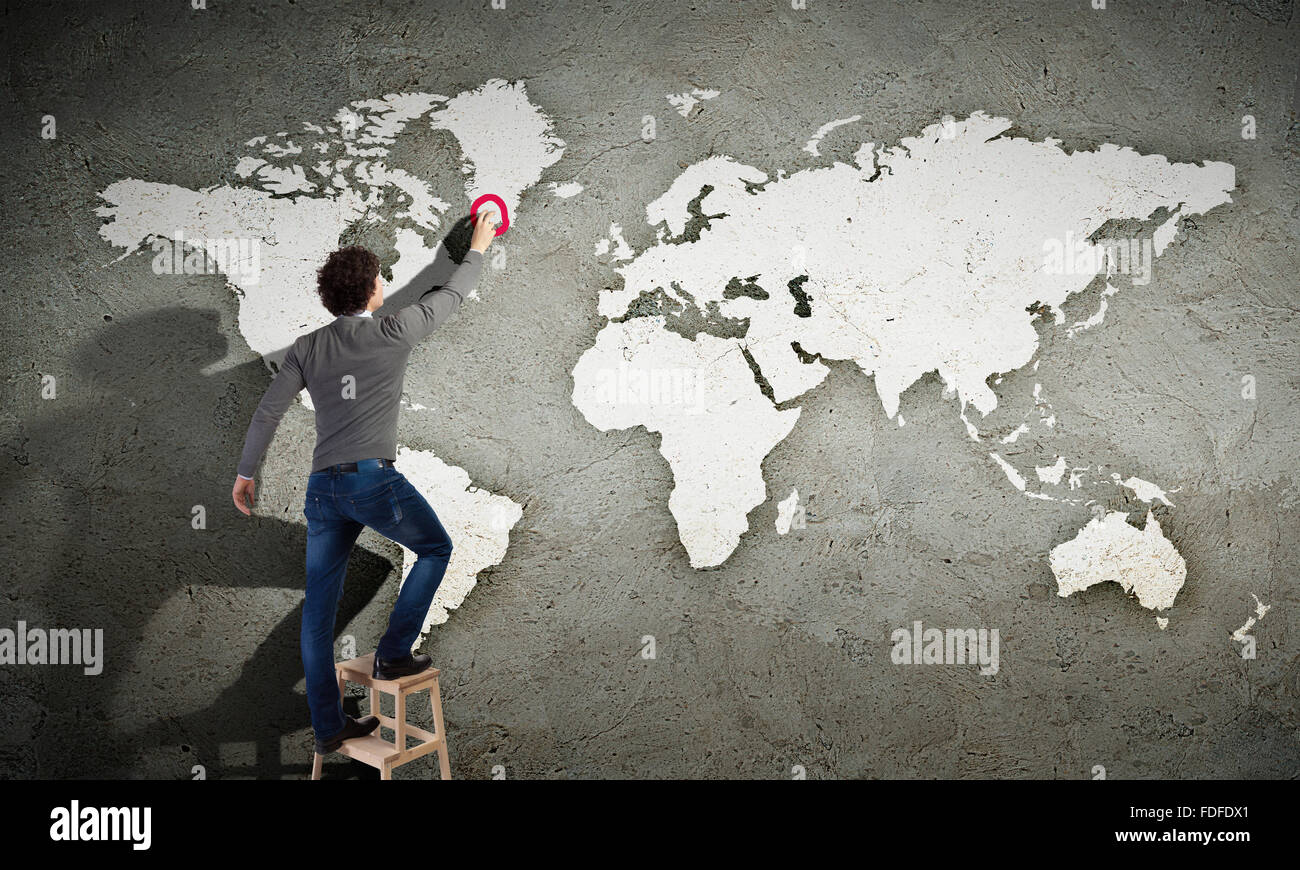 Young man drawing a world map on the wall stock photo royalty young man drawing a world map on the wall gumiabroncs Choice Image