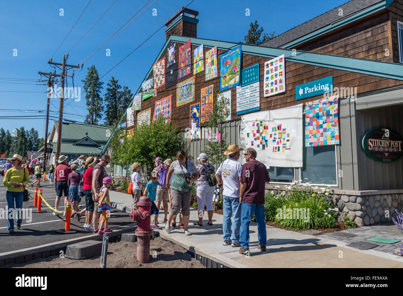 Visitors look at quilts displayed at the Sisters Outdoor Quilt ... : quilt show sisters oregon - Adamdwight.com