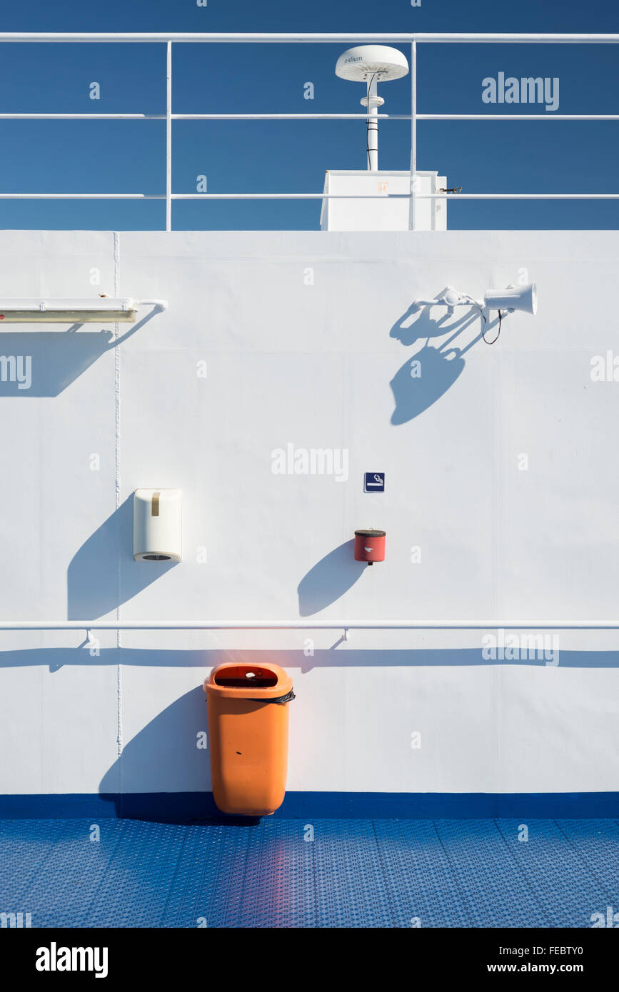 Loudspeaker,rubbish Bin,ashtray,lamp And Paper Distributor On White Wall  Behind Blue Floor On The Outer Deck Of A Passenger Ship