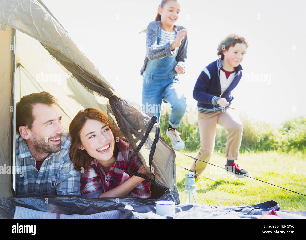Smiling couple in tent watching kids running in grass  sc 1 st  Alamy & Smiling couple in tent watching kids running in grass Stock Photo ...