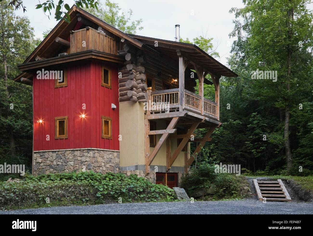 cottage style log home with stone beige stucco and red vertical cottage style log home with stone beige stucco and red vertical wood siding exterior finishes and timber wood balcony