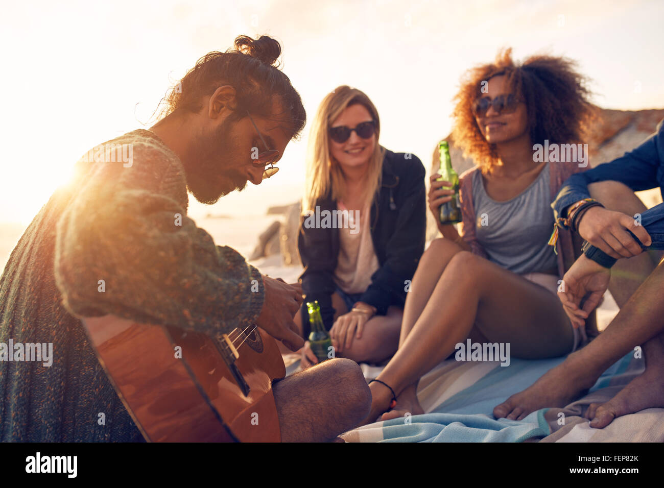 Hipster playing guitar for friends at the beach. Group of ...
