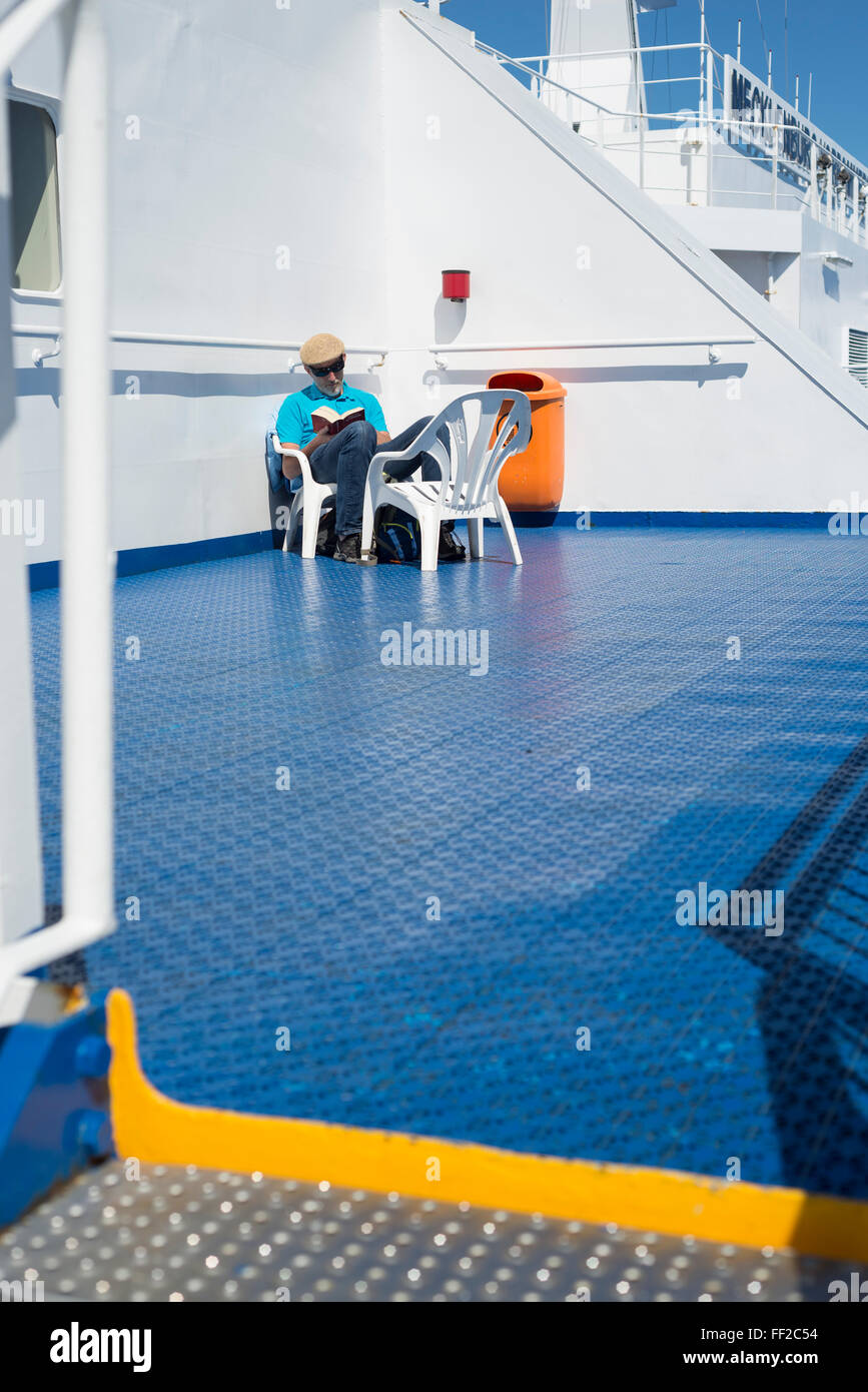 Man On A Deck Of A Ferry Ship Sunbathing And Reading A