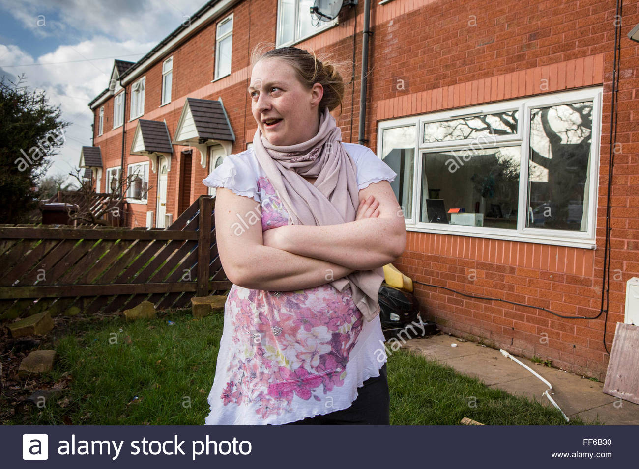 a young pregnant mother outside her house on a council estate in