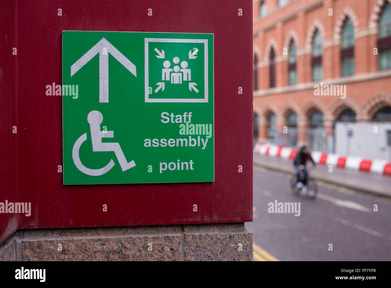 A green emergency evacuation assembly meeting point for staff the sign also shows the international symbol of access signposting people to the disability meeting biocorpaavc