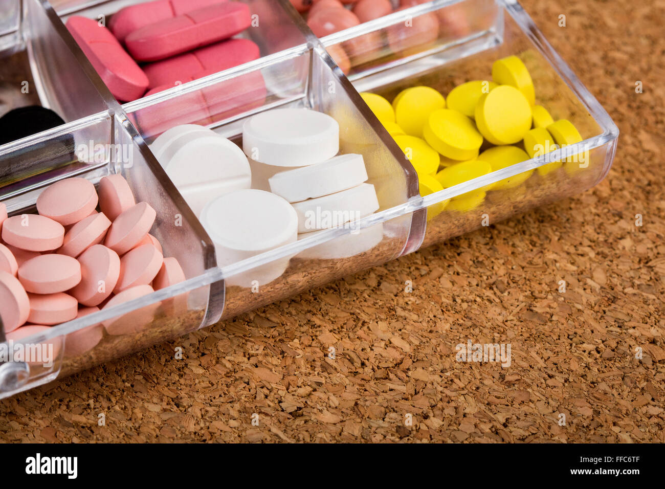 Stock Photo   Various Pills In Plastic Container On Cork Tabletop