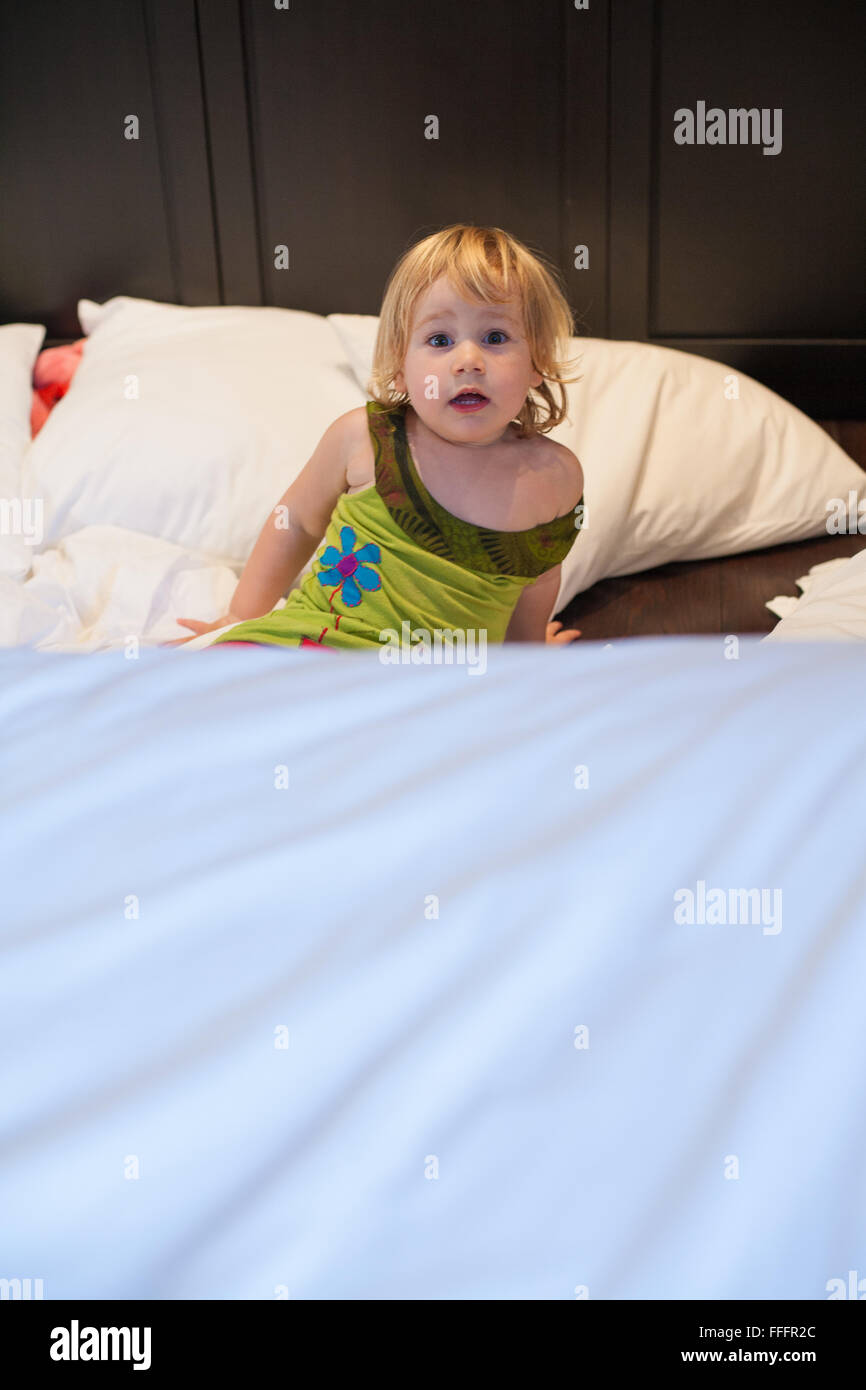 Baby bed for two year old - Stock Photo Blonde Caucasian Baby Two Years Old Green Dress Red Shorts Lying On Bed White Clothes And Cushions Crying On Dark Wood Floor