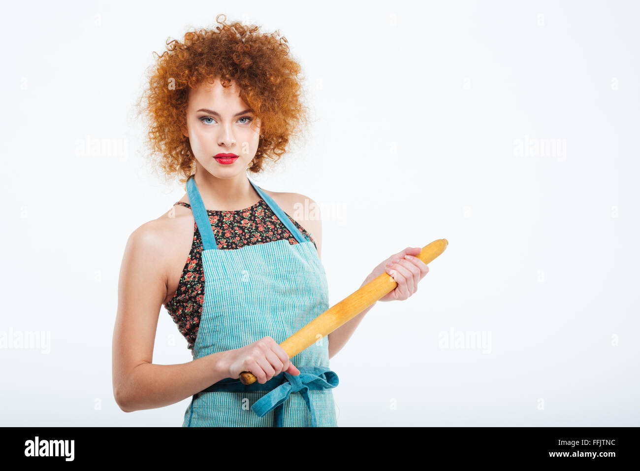 Attractive redhead housewife wearing in kitchen apron and holding ...