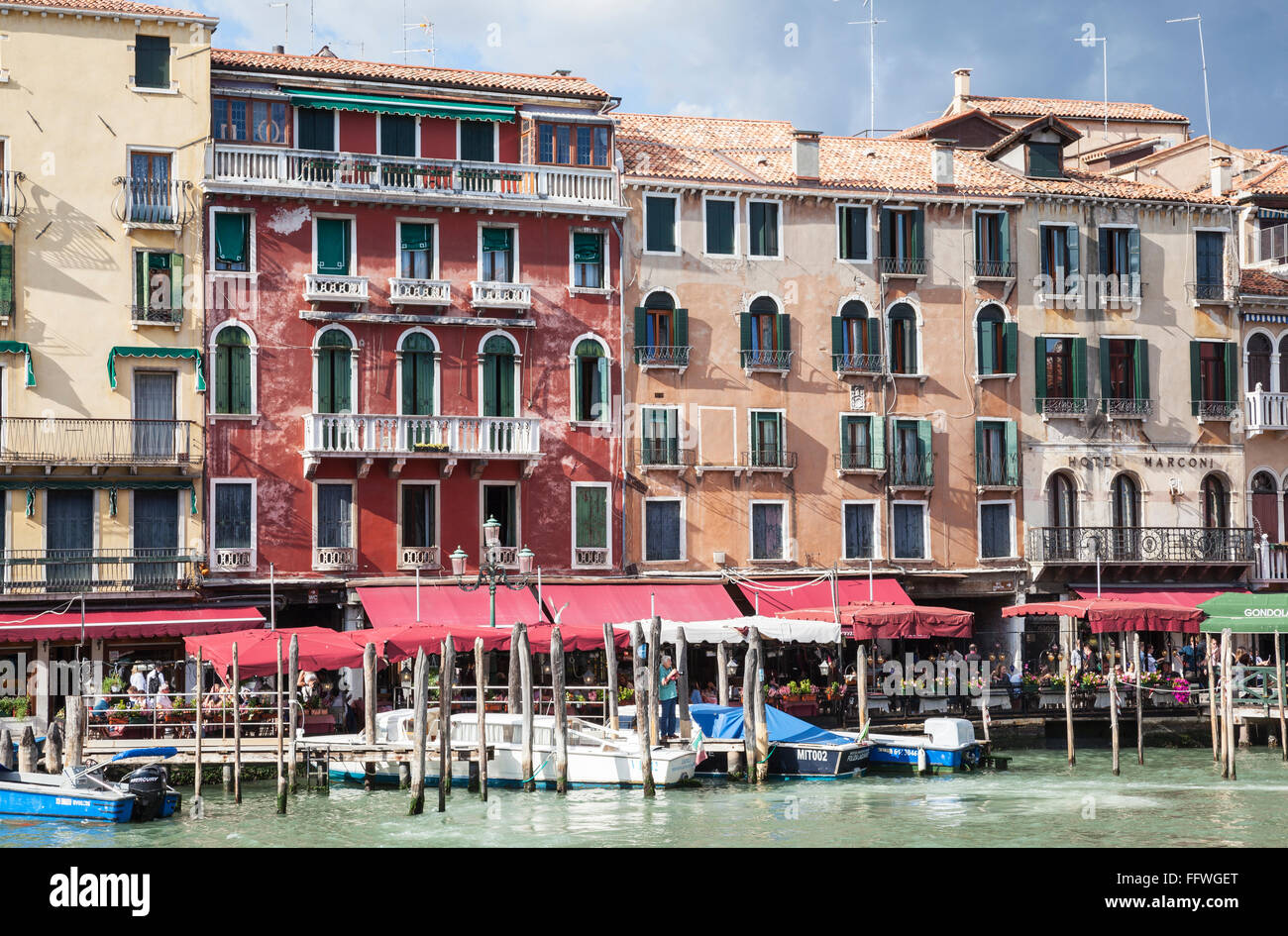 Classic Venetian buildings, boat moorings and cafes on a sunny day along  the Grand Canal in Venice