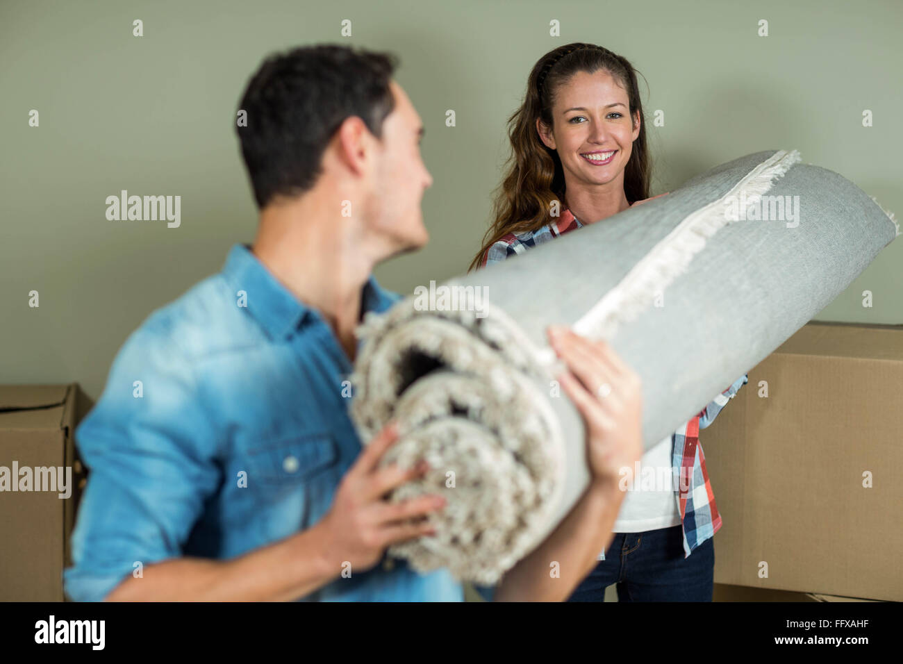 Happy Couple Carrying Rolled Up Rug