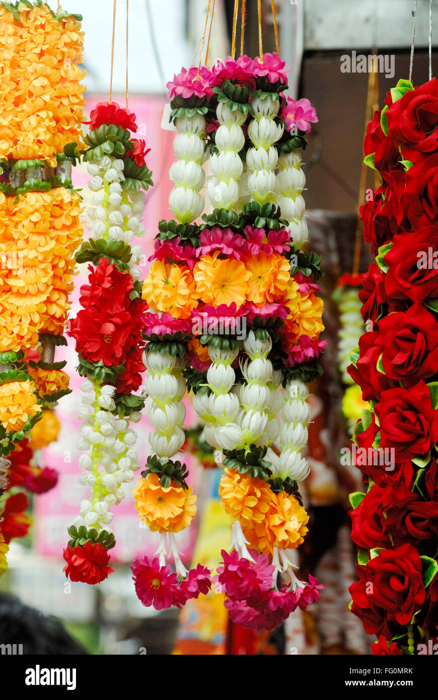 Colourful garlands of artificial flowers hang for sale for Artificial flower decoration for ganpati