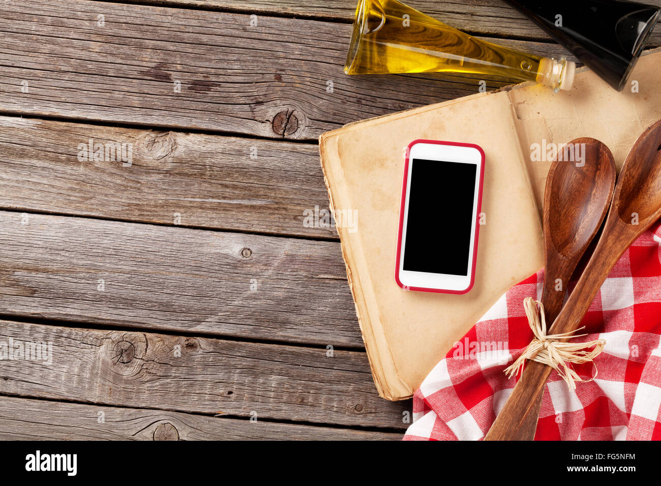 kitchen table with ingredients, utensils and smartphone with blank