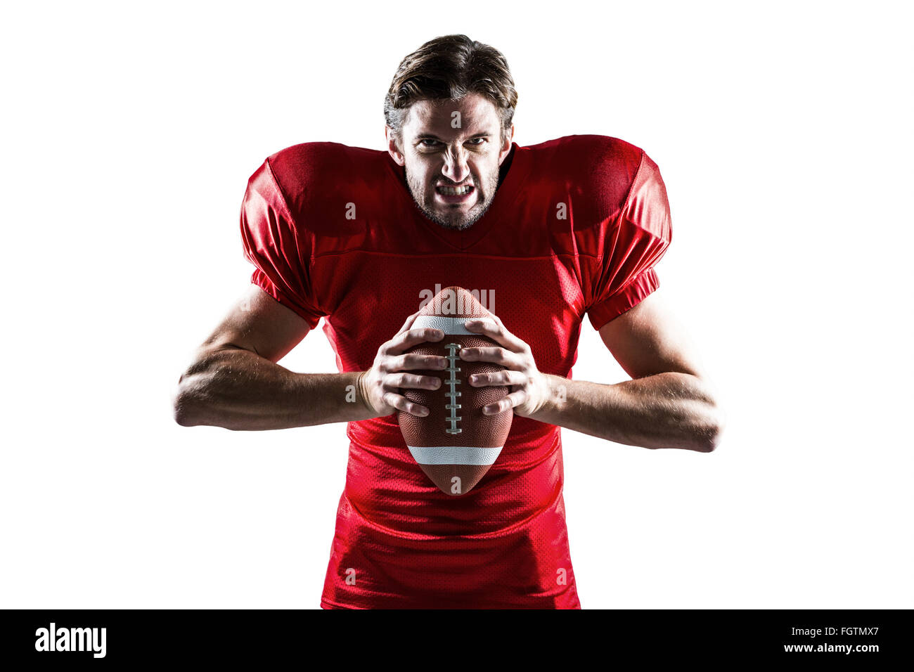 angry american football player in red jersey holding ball stock