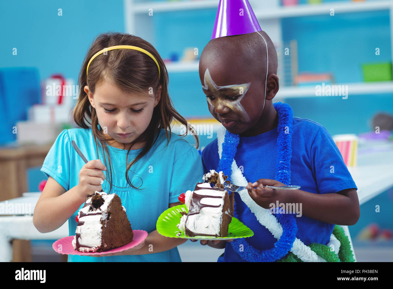 Happy kids eating birthday cake Stock Photo Royalty Free Image