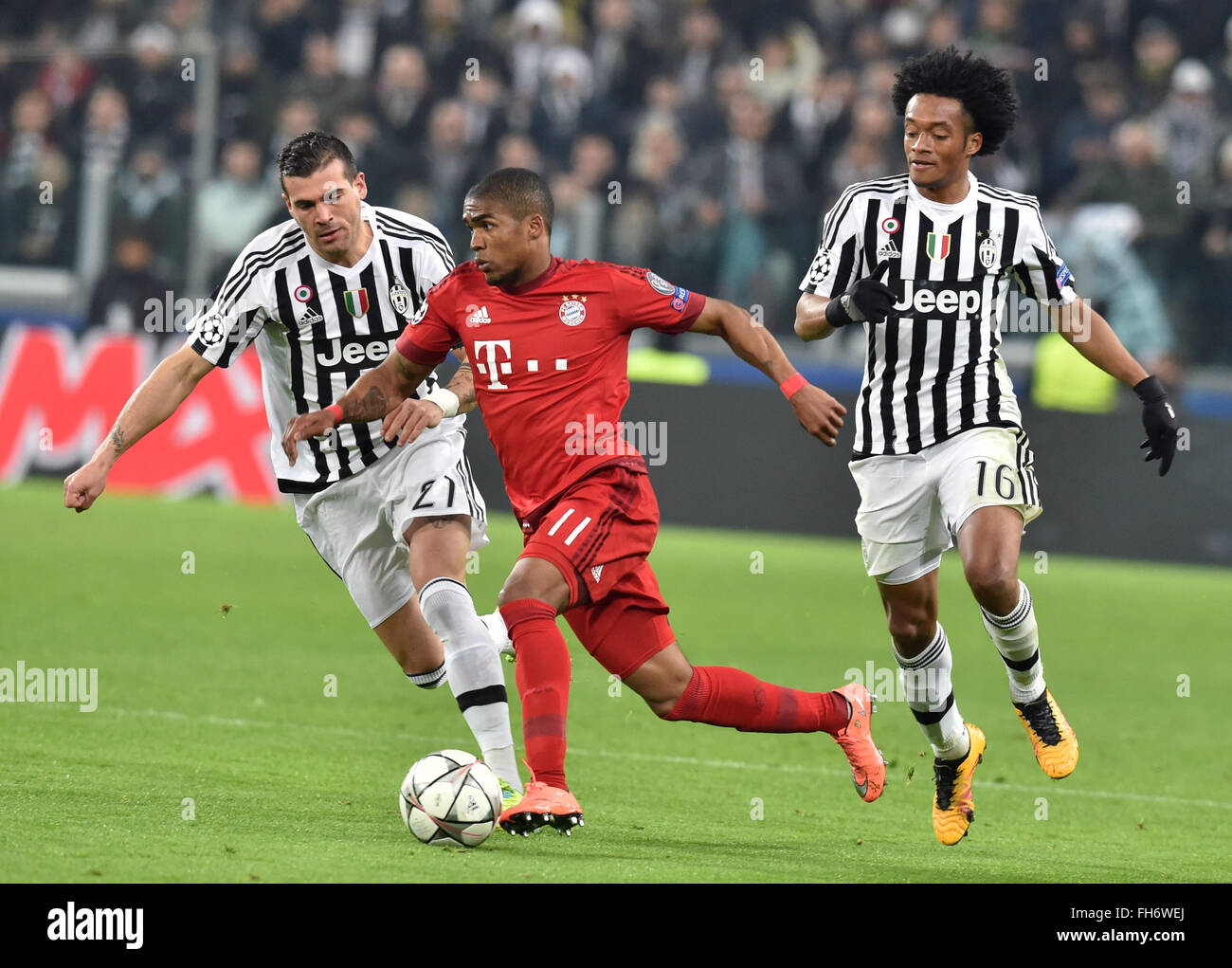 Munich s Douglas Costa C vies for the ball with Juve s Stefano