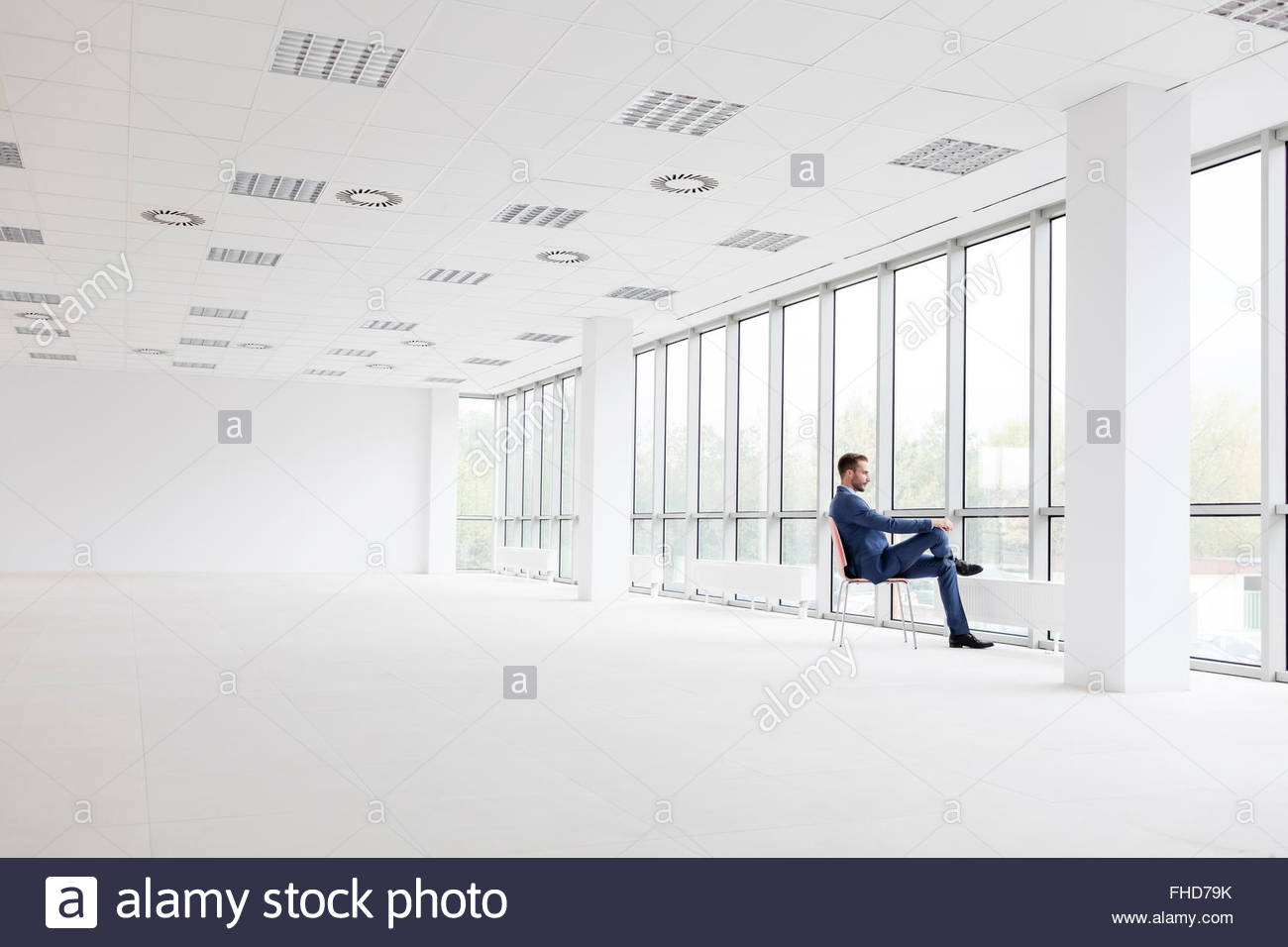 Empty Office Room With Window Cloudiasouvenir Com - Businessman in empty office looking out of window stock image