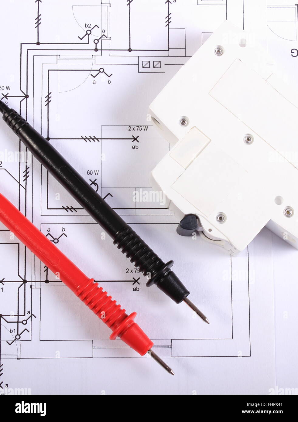 cables of multimeter and electric fuse lying on construction drawings of house electrical drawings and tools for engineer jobs