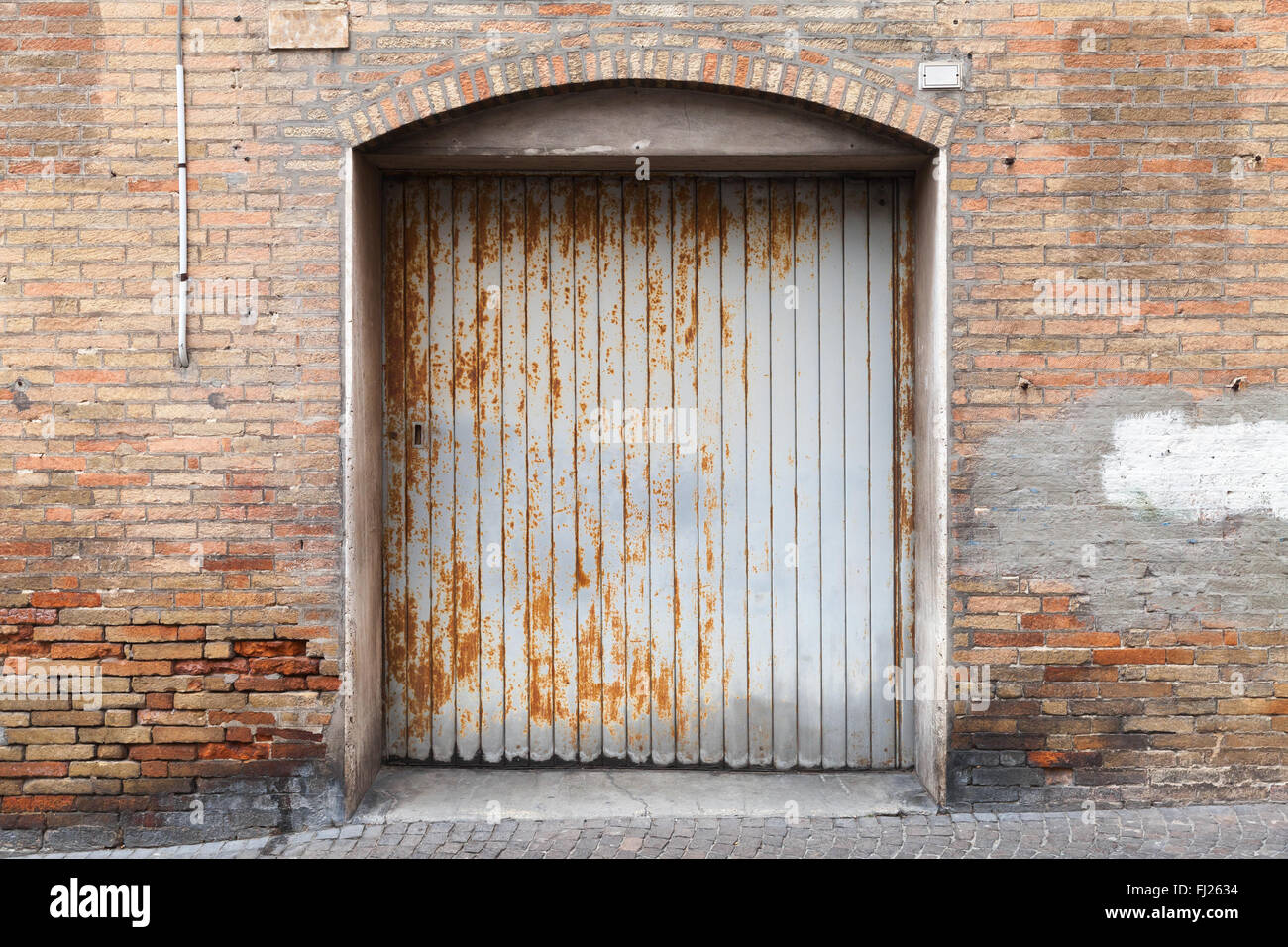 Rusted grungy metal gate in old brick wall background