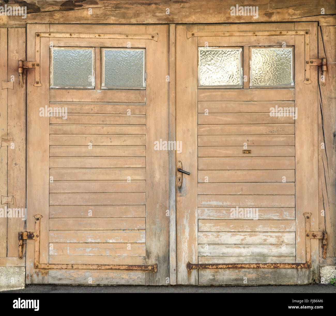small garage doorOld light brown dirty and weathered wooden garage door with four