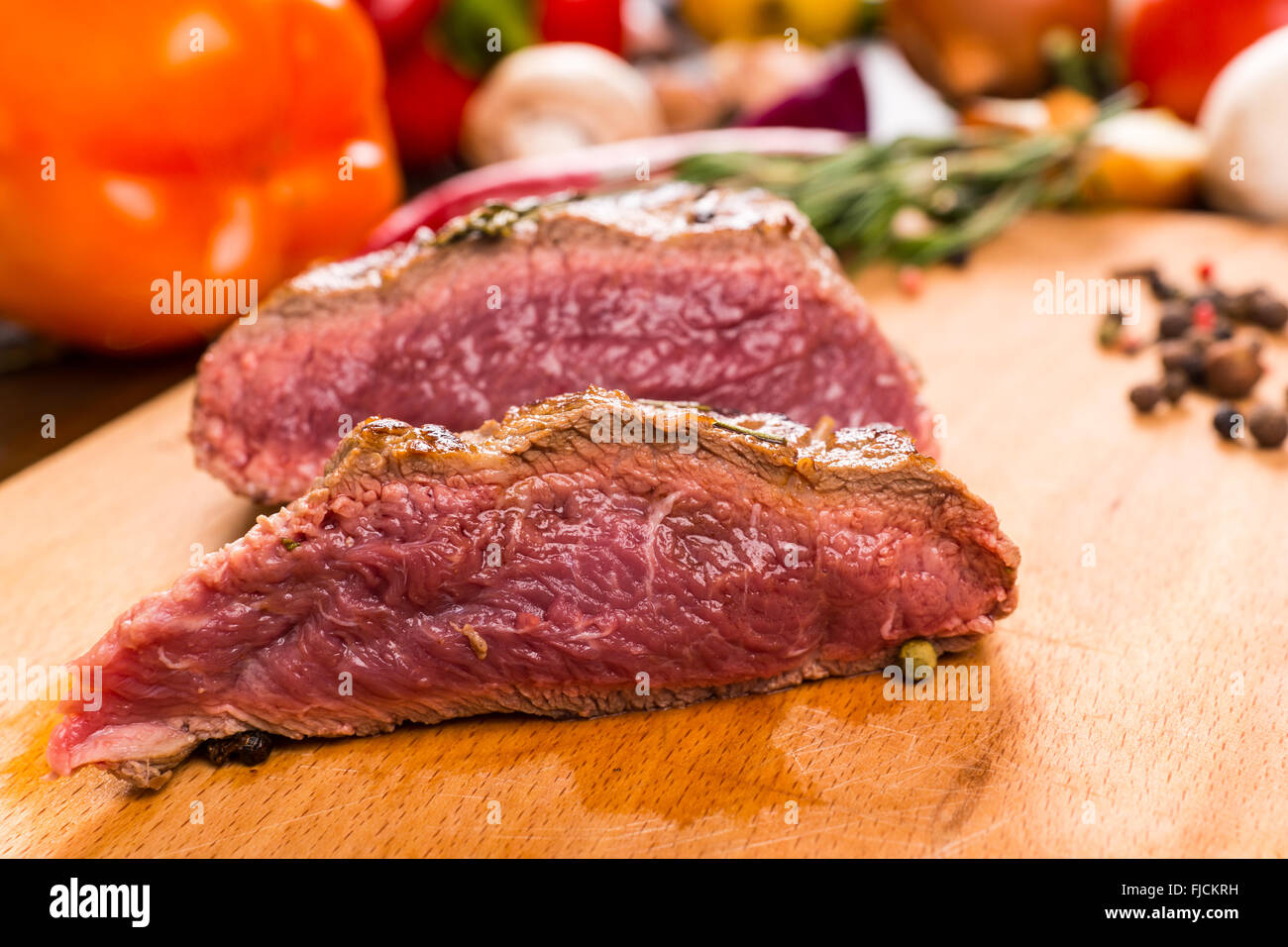 Sliced roast beef package - Close Up Still Life Of Rare Cooked Roast Beef Sliced In Half And Resting On Wooden Cutting Board With Fresh Vegetables Herbs And Spices In Background