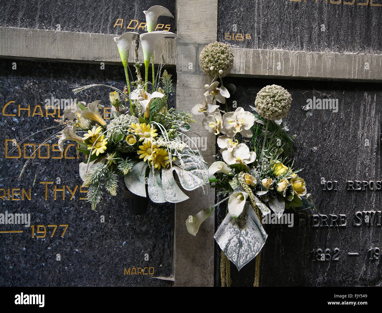 Dusty fake flowers decorating graves in the catacombs of laken ...