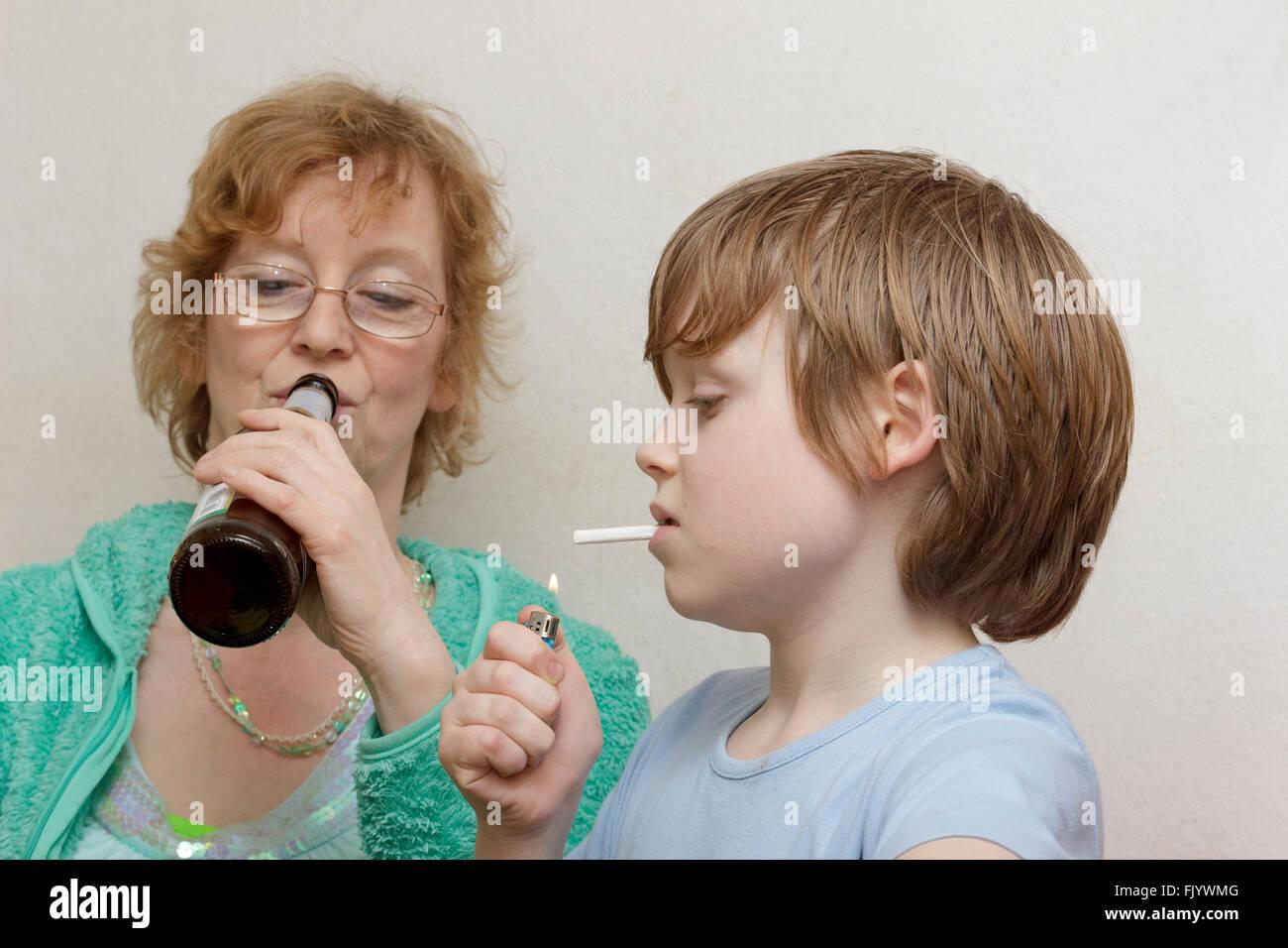underage smoking underage boy smoking, his mother drinking beer - Stock Image