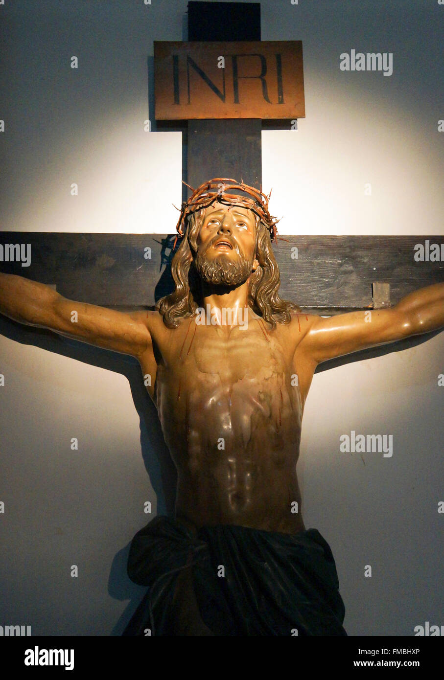 statue of jesus hanging on a cross with light on his face stock