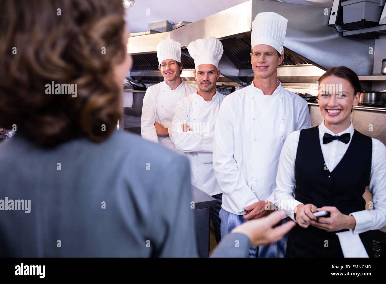 Restaurant Kitchen Staff restaurant manager briefing to his kitchen staff stock photo