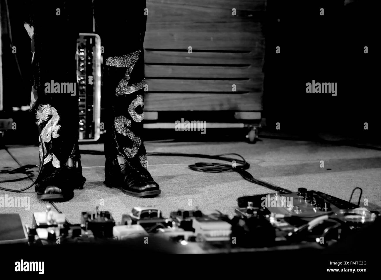 Guitar Pedals On Concert Stage In Black And White With Feet