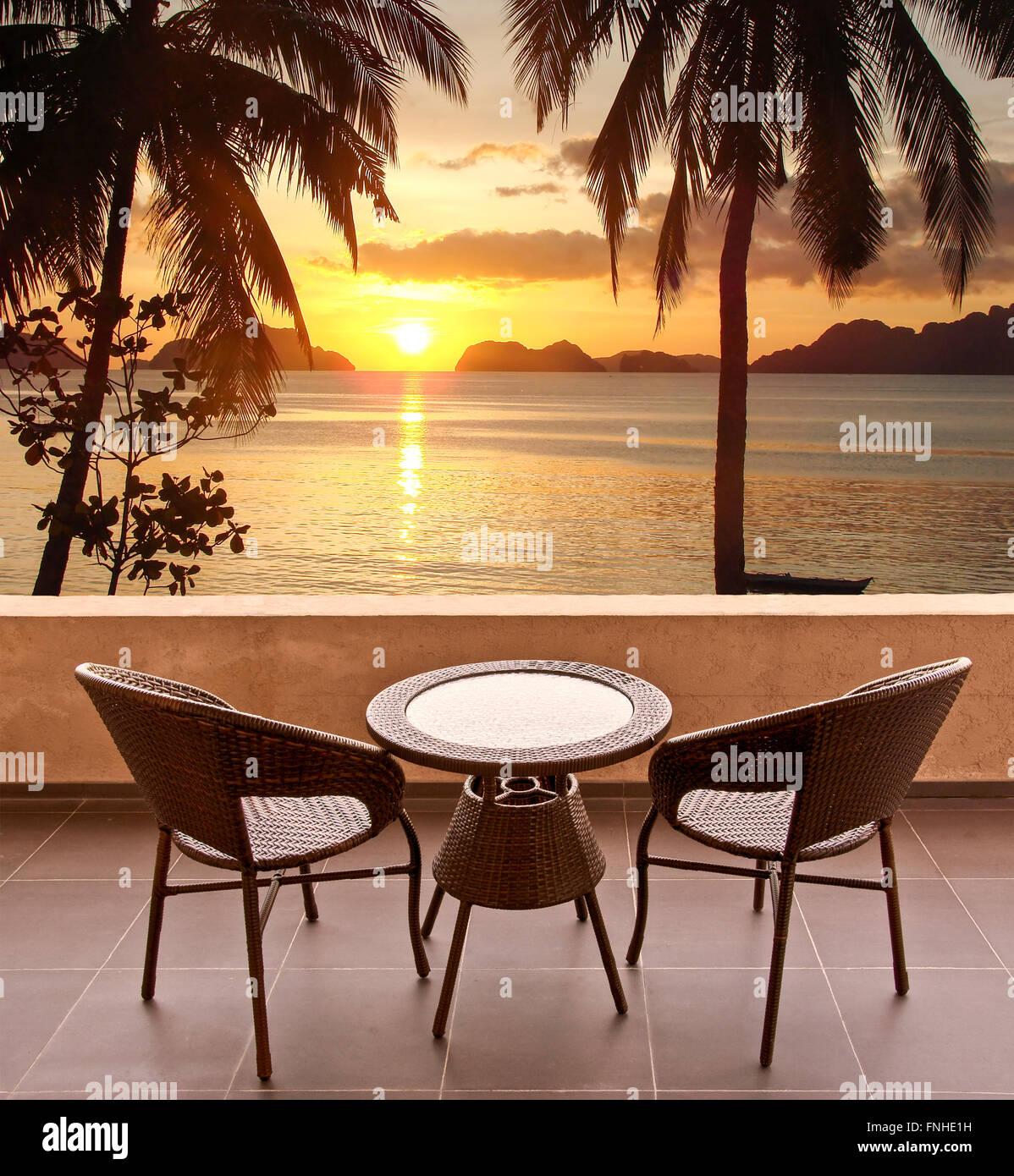 Beach sunset with chairs - Stock Photo Table And Chairs On A Terrace View On A Tropical Beach At Sunset