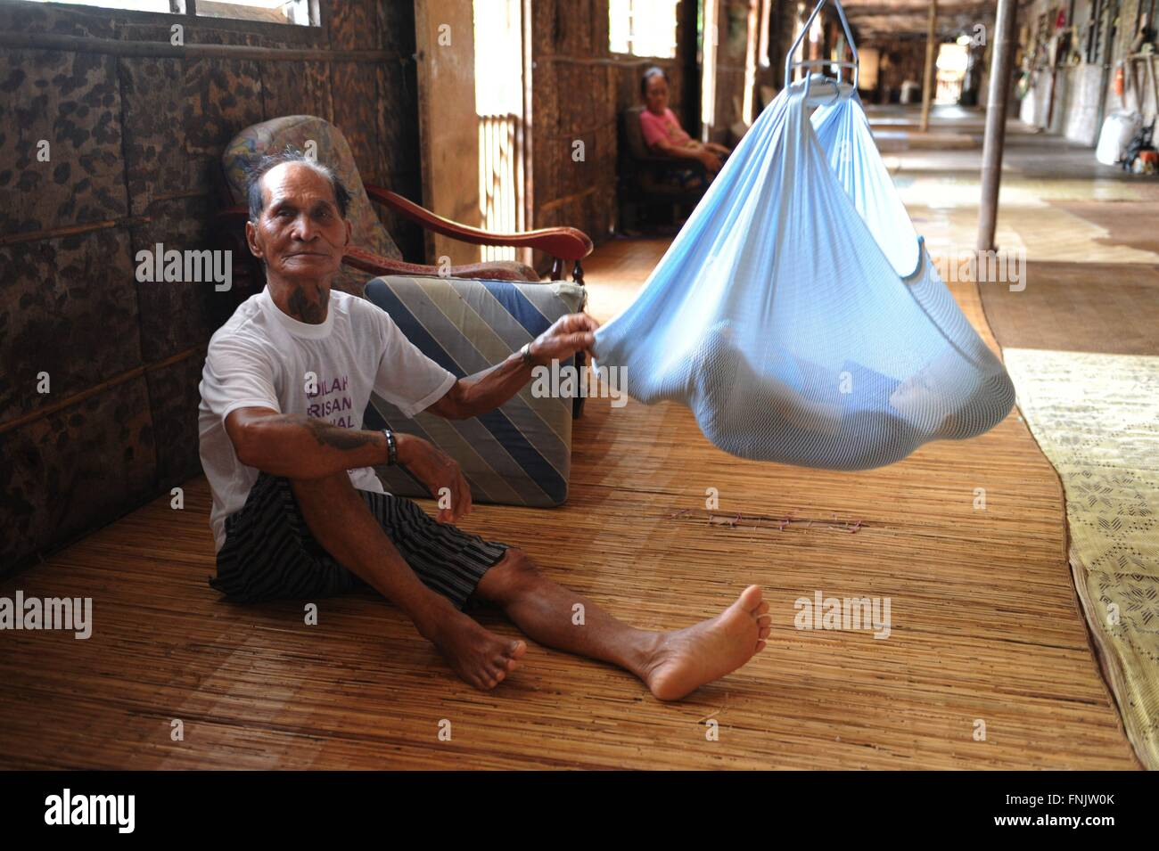 an iban man is sitting next to his grandchild who is lying in a baby hammock inside a traditional iban longhouse near lubok antu malaysia 23 october 2014  an iban man is sitting next to his grandchild who is lying in a      rh   alamy