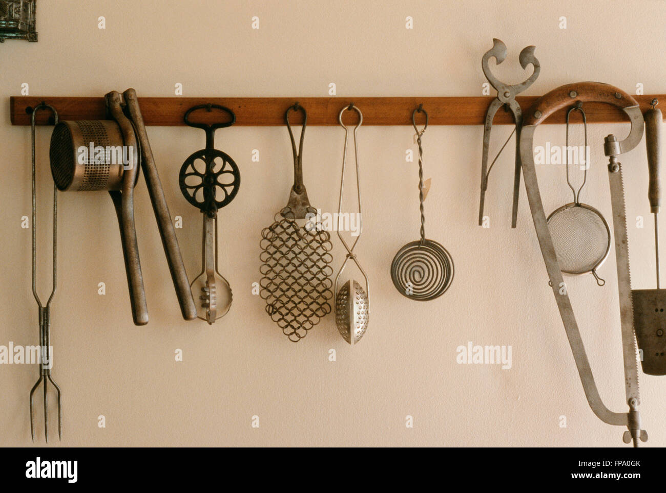 Vintage Kitchen Gadgets; Vintage Kitchen Gadgets Hanging From A Rack    Stock Photo
