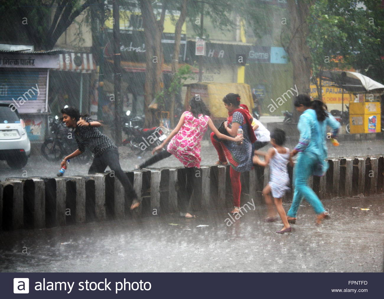 indian-women-and-children-run-to-take-cover-from-heavy-rain-in-bhopal-FPNTFD