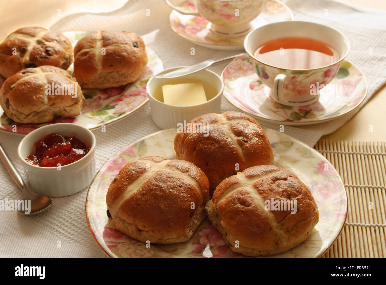 table set with hot cross buns and tea for easter stock photo