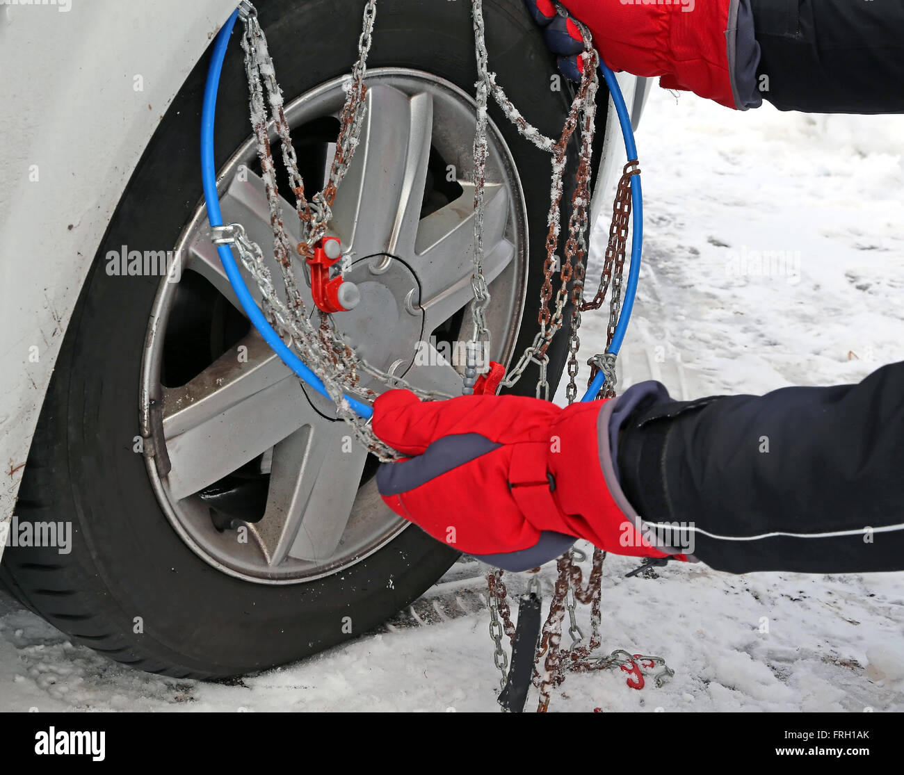 man with red gloves install snow chains in the car tyre in winter on stock photo royalty free. Black Bedroom Furniture Sets. Home Design Ideas