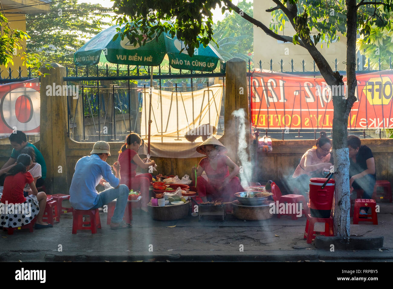 Stock Photo - People eating at street food stall on the sidewalk in Hoi An, Vietnam