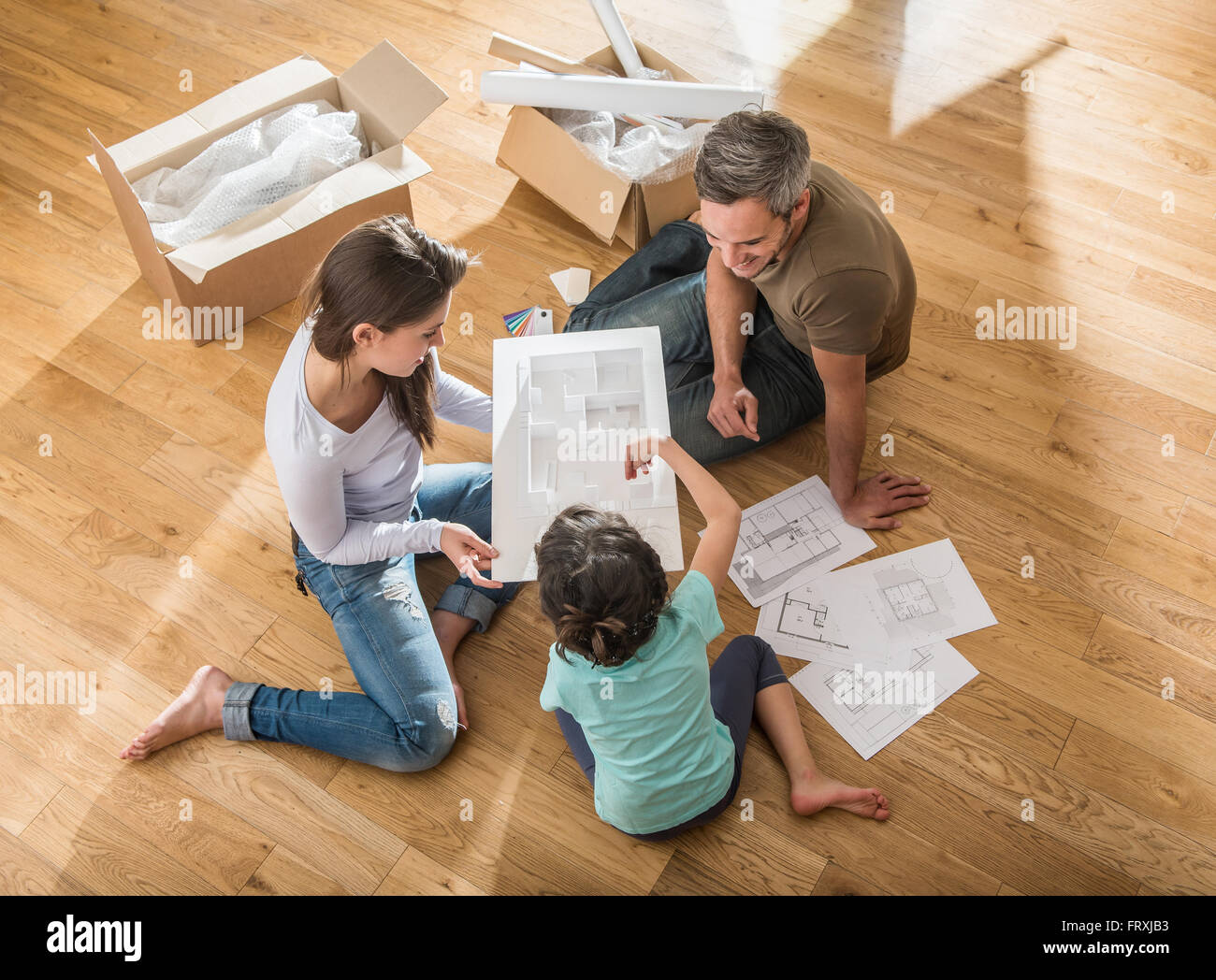 Happy parents are sitting barefoot on the floor of their new house happy parents are sitting barefoot on the floor of their new house they are looking at the house model with their daughter they malvernweather Images