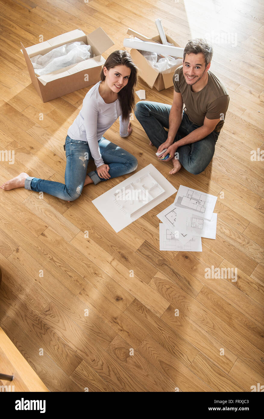 Nice couple in casual clothes sitting barefoot on the wooden floor nice couple in casual clothes sitting barefoot on the wooden floor of their new house malvernweather Images