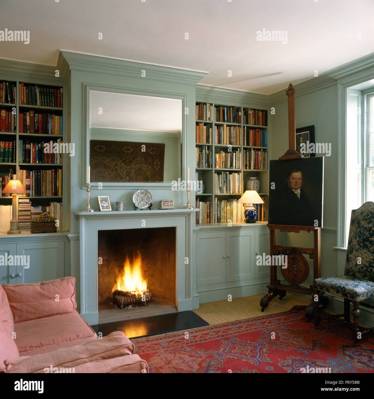 mirror above fireplace with lighted fire in pale turquoise sitting