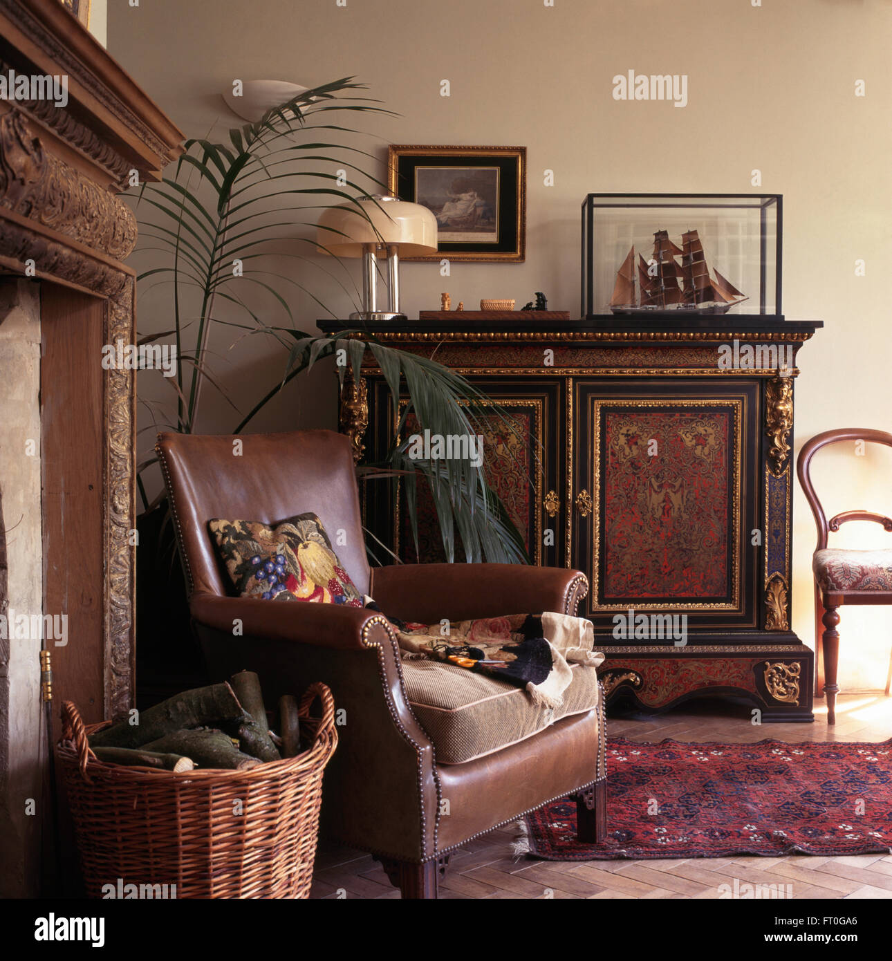 Brown leather chair and ornate antique cupboard in old fashioned ...