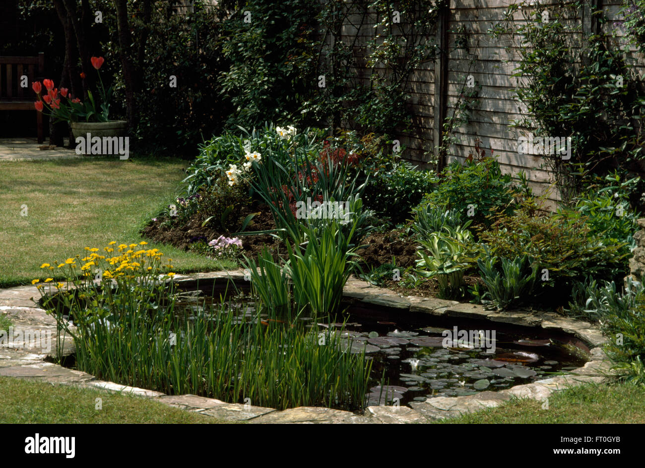 Stone paved edging around a curved pond with yellow for Garden pond edging