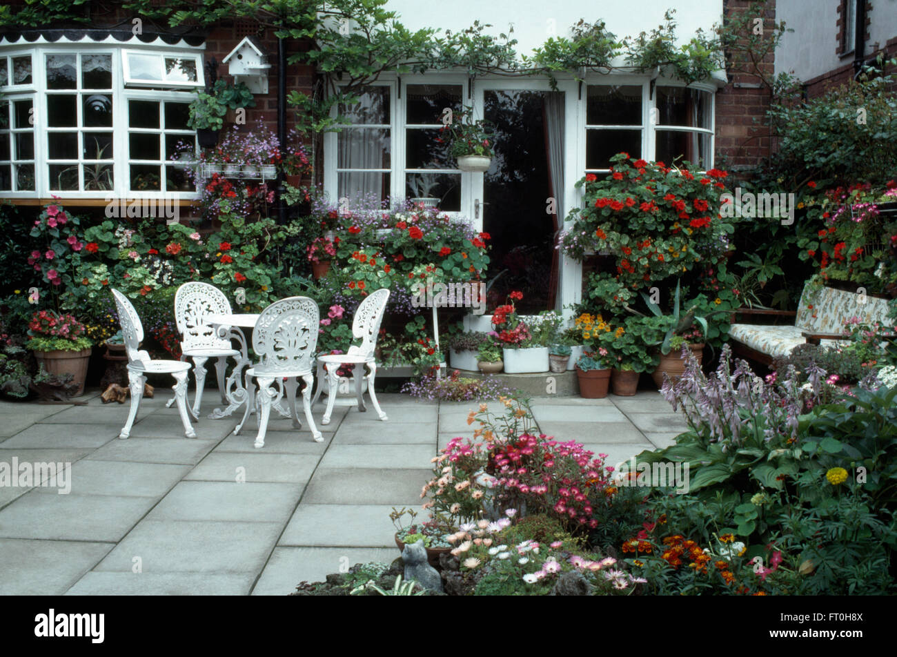 White Wrought Iron Table And Chairs Part - 33: Stock Photo - White Wrought Iron Table And Chairs On Paved Patio In Front  Of French Windows Of Suburban House