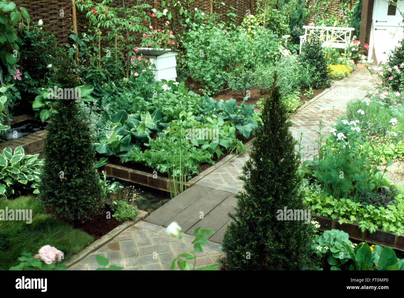 Box Pyramids Either Side Of A Paved Path In Small Well Maintained Vegetable Garden With White Bee Hive And Stream